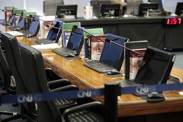varios computadores em uma mesa com livros e uma faixa do CNJ cercando