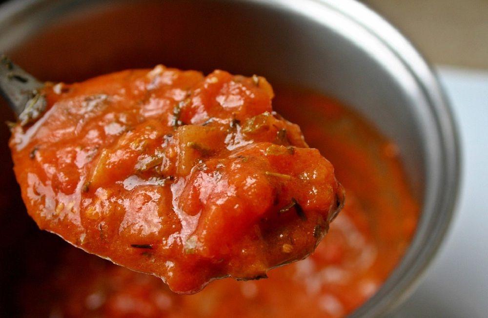 Colher de molho de tomate com panela ao fundo