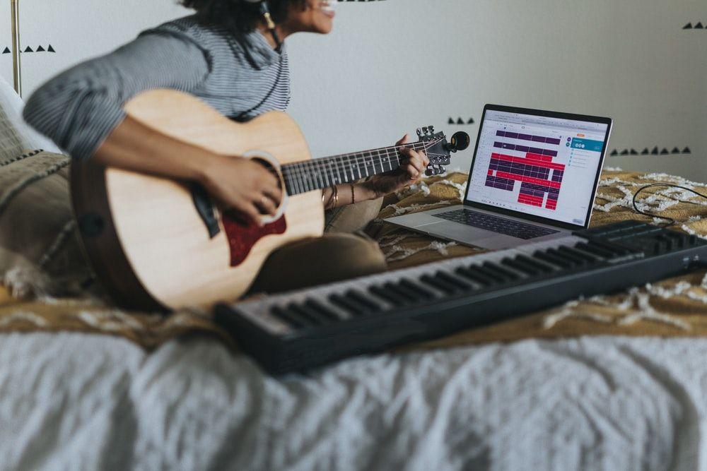 man in gray t-shirt playing guitar