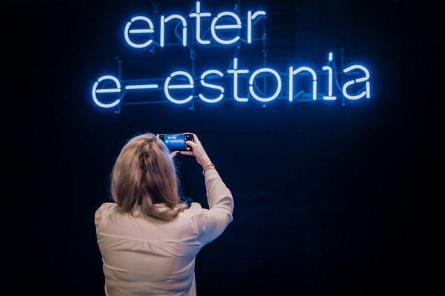 mulher tirando foto de parede com texto luminoso escrito enter e-estonia