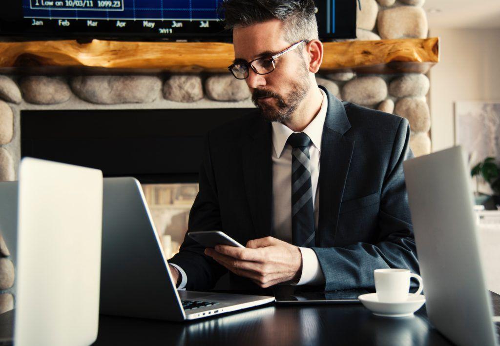 Homem de terno com celular na mo de frente para o computador Pode ser um advogado em uma audincia virtual
